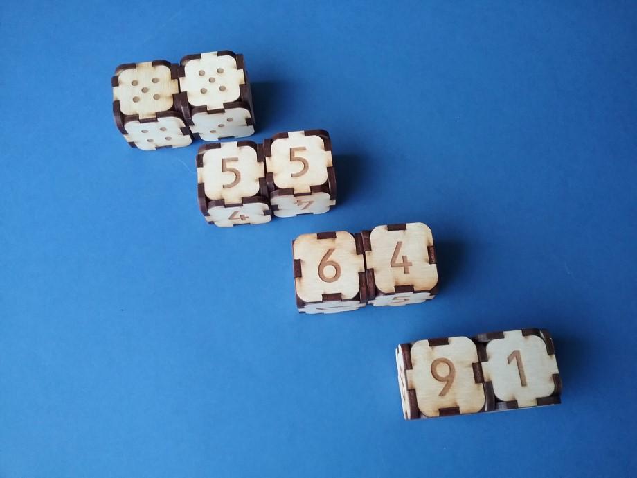 """Attēlot uz metamajiem kauliņiem redzamos skaitļus, visos iespējamos veidos izmantojot ciparu klučus. Piemēram, skaitli ''10'' iespējams attēlot gan kā ''6'' un ''4'', gan kā ''5'' un ''5'' u.t.t. (Veidojam skaitļu ''mājiņas"""")."""