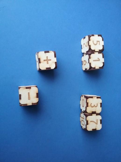 """Ripināt divus ciparu klučus, nosaukt divciparu skaitli, kas izveidojies. Darot to arī ar otru kluču pāri, veikt aritmētiskās darbības ar abiem divciparu skaitļiem. Izmantojot trīs klučus vienlaicīgi, var pieskarties arī skaitļu šķirai """"simti""""."""