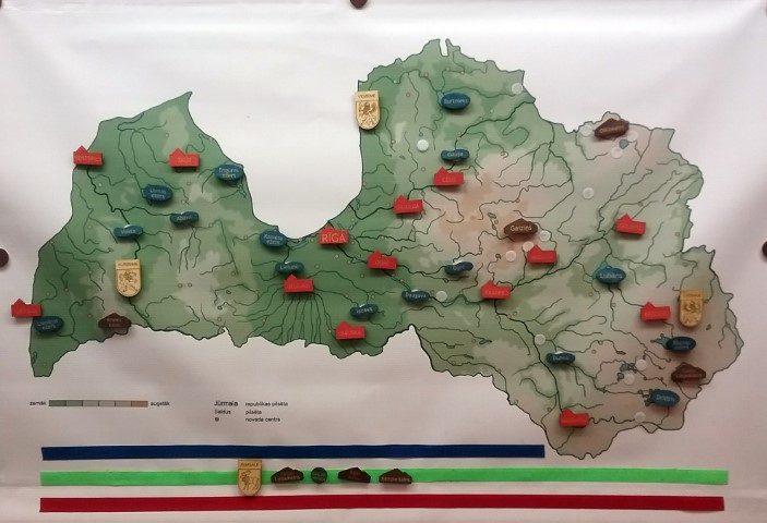 """Latvijas karte ar Latvijas ģeogrāfisko objektu (pilsētu, upju, ezeru, pauguru un īpašu dabas objektu) nosaukumiem,  kuri ir piestiprināmi pie kartes, tādējādi, dodot iespēju daudziem interesantiem uzdevumiem mācīšanās procesā  kā arī pārbaudes darbos.  Komplektā ietilpst: Latvijas karte (piekarināma pie tāfeles vai sienas, vai arī piestiprināma  ar magnētu palīdzību), dažādu krāsu kauliņu komplekts ar Latvijas ģeogrāfisko objektu nosaukumiem un neliela koka Latvijas karte -""""leģenda"""" ar uzrakstītiem Latvijas ģeogrāfisko objektu nosaukumiem."""